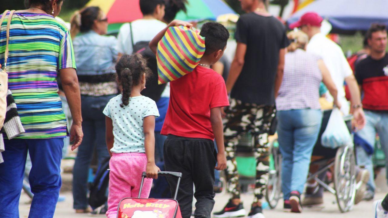 Un grupo de pasajeros consulta los vuelos en el Aeropuerto de Asturias.Migrantes venezolanos llegados a Colombia