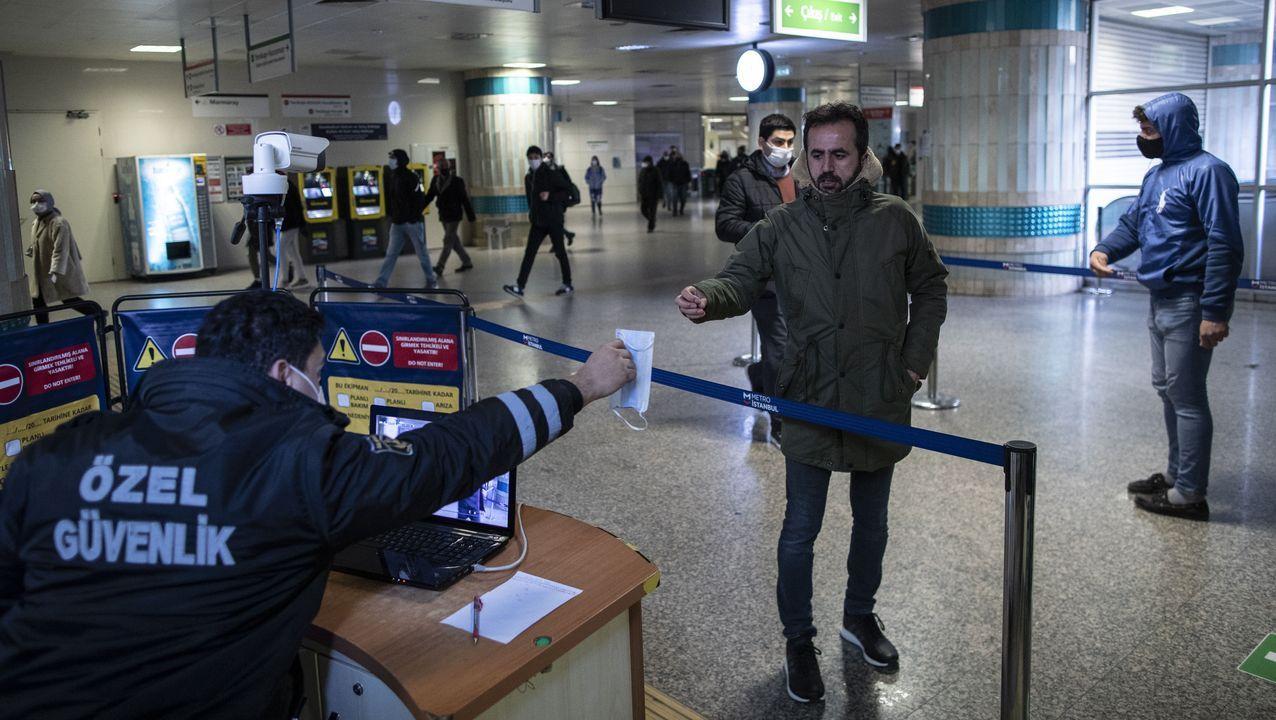 Un oficial de seguridad le entrega una mascarilla a un pasajero del metro de Estambul