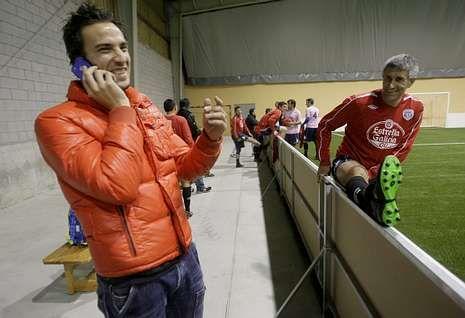 romeo.Óscar Díaz, hablando por teléfono, junto a Quique Setién antes de un partido de fútbol indoor.