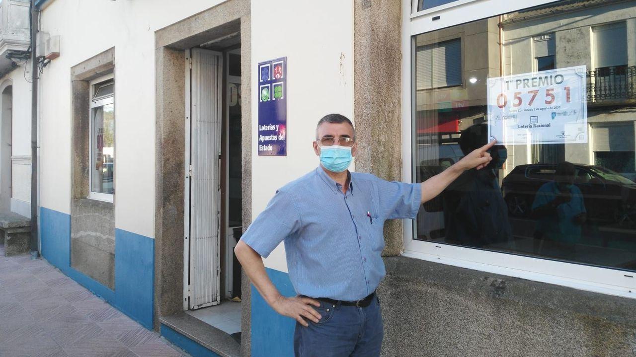 Manuel Domínguez, del bar A Quiniela de Zas, con el cartel que acredita el primer premio de la Lotería Nacional de hoy sábado, EL 05.751 (inicialmente Loterías mandó un cartel equivocado acabado en 31)