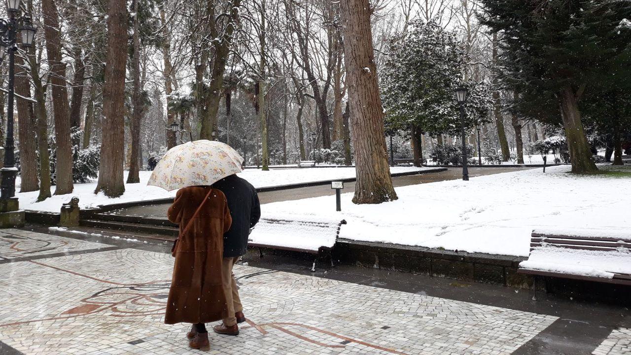 Nieve en Oviedo.Una pareja pasea cubriéndose de la nevada junto al Parque San Francisco