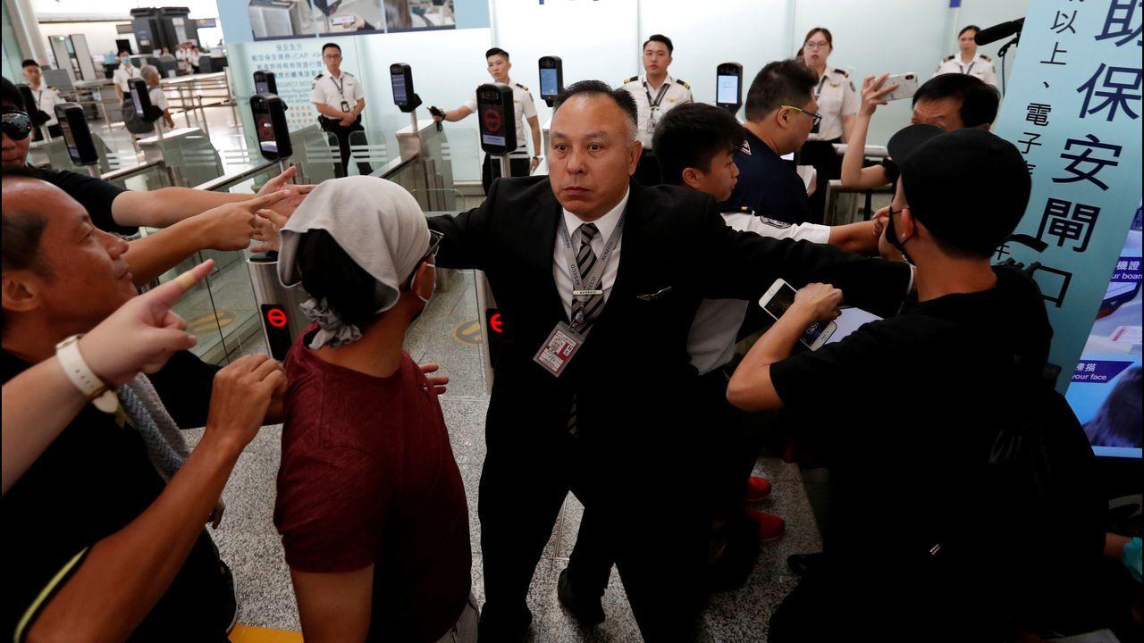 Un miembro del aeropuerto de Hong Kong intenta contener a los manifestantes ante el mostrador de una compañía aérea