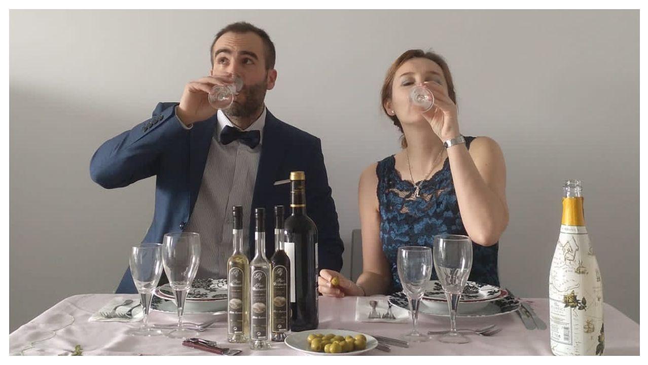 Una pareja asistente a la boda por Skype bebe vino espumoso en su propio domicilio tras el brindis por los recién casados