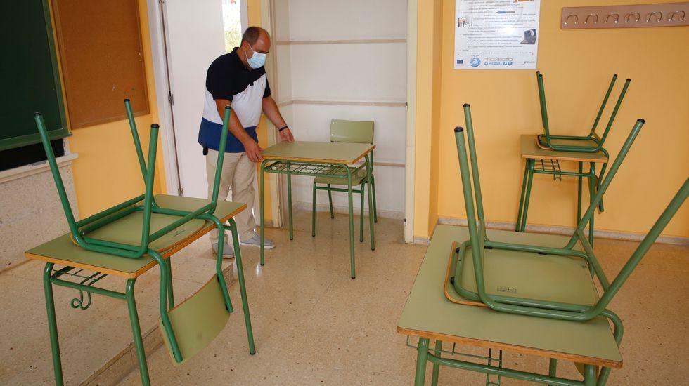 El director del IES Xunqueira II, Juan Carlos Pérez Mestre, coloca un pupitre en el espacio interior de un armario, que se desmontó para ganar la máxima superficie al aula