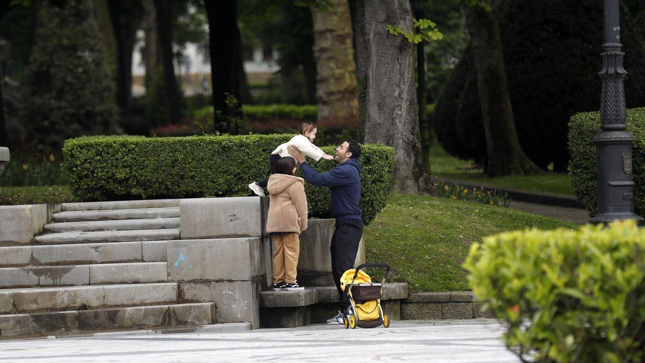 Un hombre juega con sus hijas en un parque del centro de Oviedo,