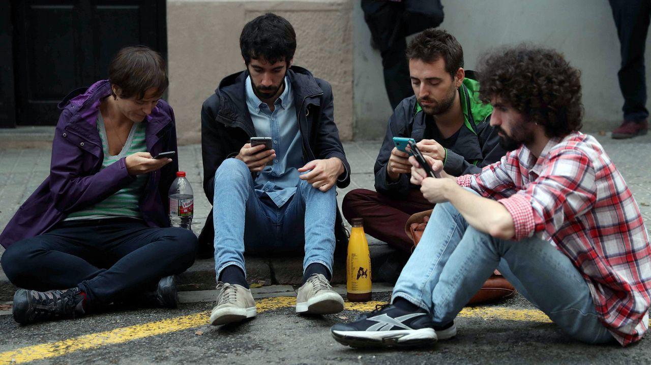 Unos jóvenes que permanecen en las inmediaciones del colegio electoral al de la Escola Jaume I en el barrio de Sants de Barcelona.