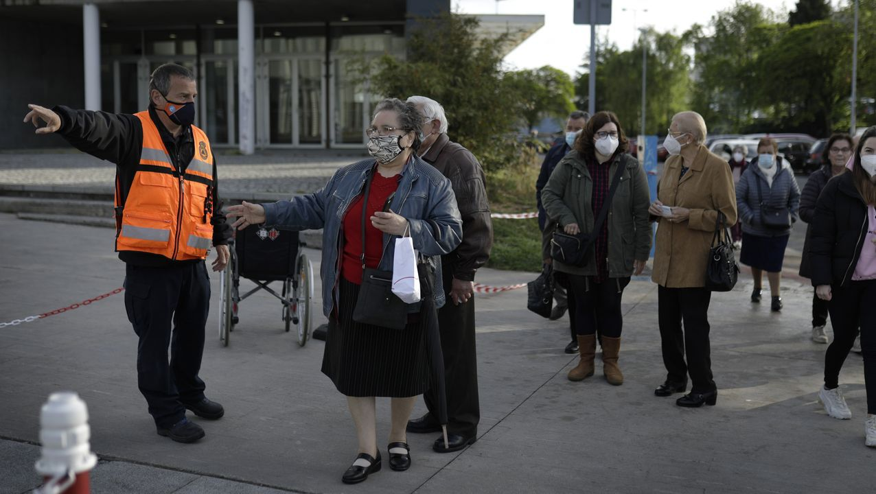 Vacunación masiva frente al covid en Expocoruña para personas de 75 a 79 años. Miembros de Protección Civil orientando en la entrada a los citados