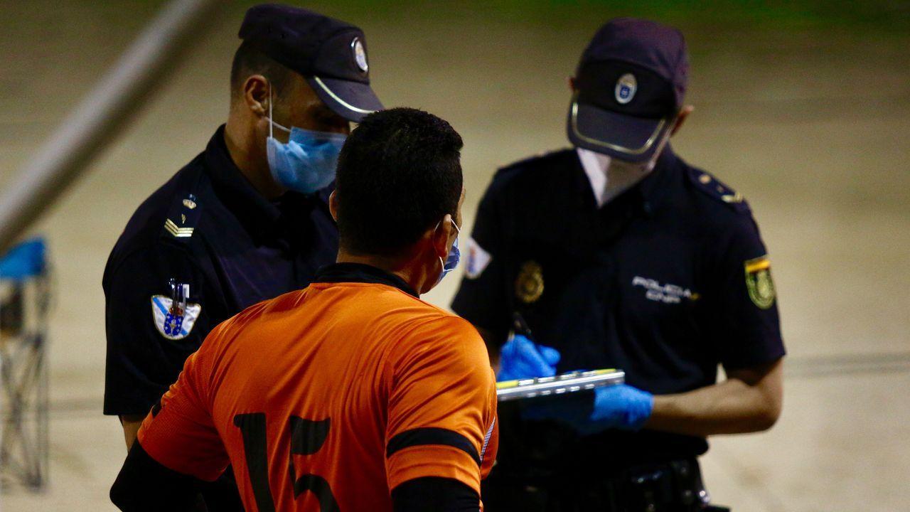 ¡Cómo estaba la playa!.Dos policías autonómicos en A Coruña, identificando a un vecino que practicaba deporte en grupo sin mascarilla