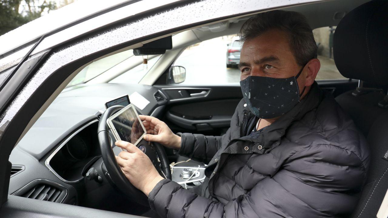 La falta de clientes condena a los taxistas compostelanos a eternas esperas en las paradas que muchos, como Manuel Pena (en la imagen), sobrellevan gracias a poder ver series en las tabletas o los móviles