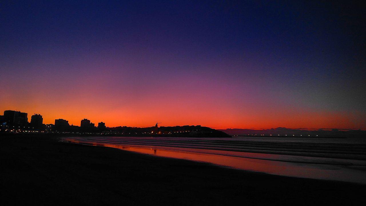 Fenómeno óptico de la luz crepuscular (esas tonalidades anaranjadas y rojizas hacia el lado donde se pone el astro-rey, es decir, hacia el Oeste. En menor medida también se puede observar la luz púrpura. Paseo del muro de San Lorenzo a la altura de la caseta de salvamento, Gijón