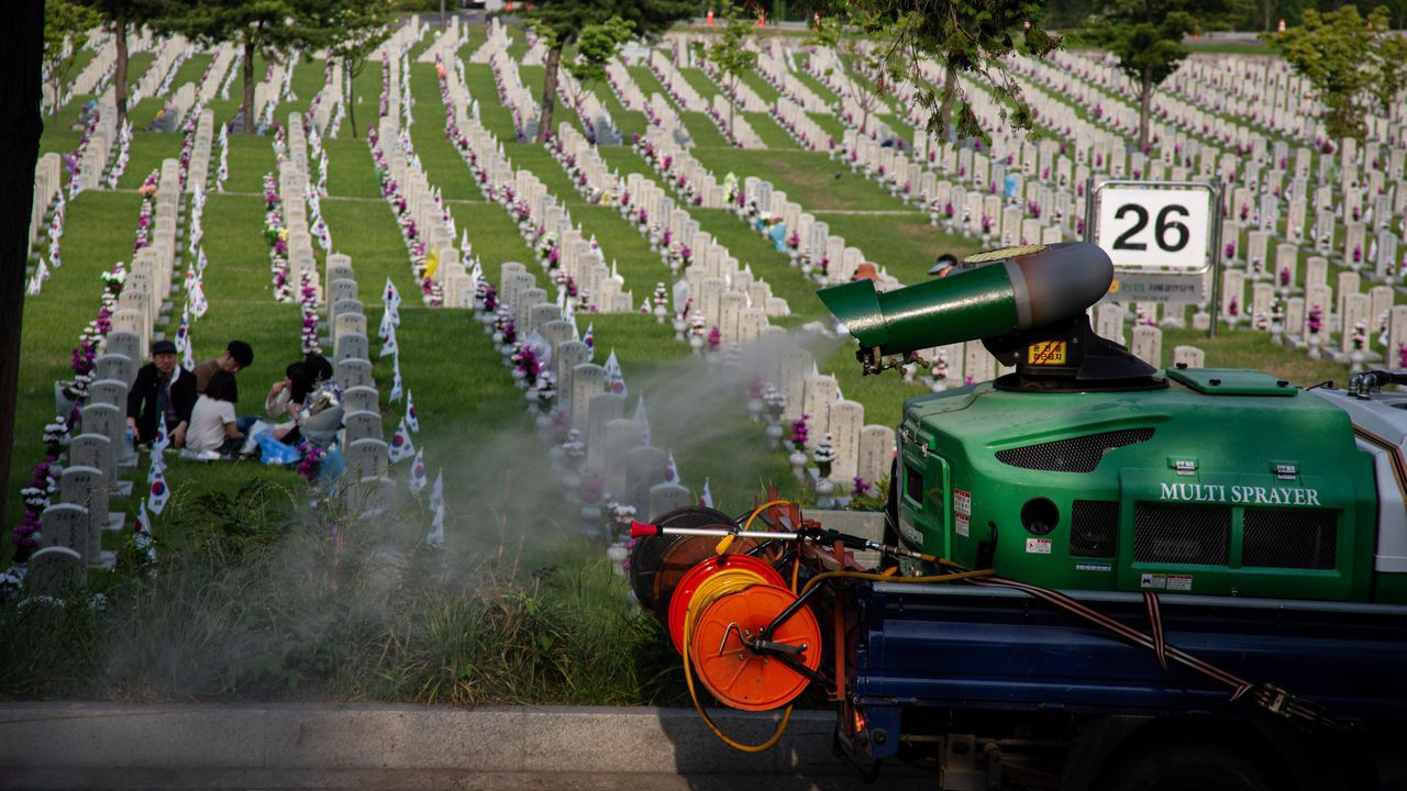 Un camión fumigador desinfecta un cementerio en Seúl