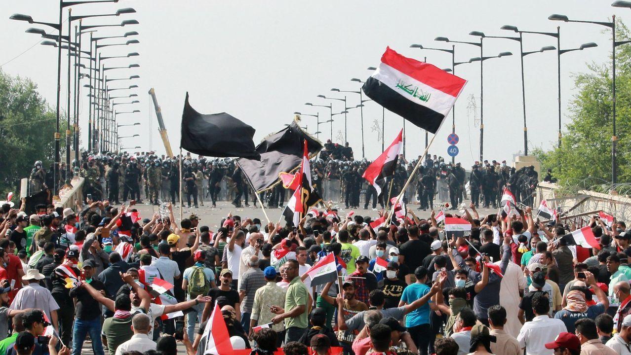 La ría y el puerto de Avilés.Varios manifestantes evacuan a un hombre afectado por los gases lacrimógenos durante las protestas en Bagdad