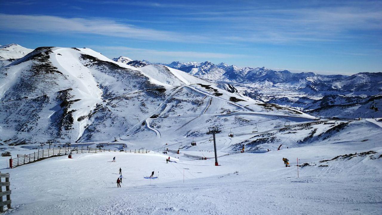 Los esquiadores disfrutan de la nieve con la estación de esquí de Valgrande-Pajares al fondo.Estación de Valgrande Paajres
