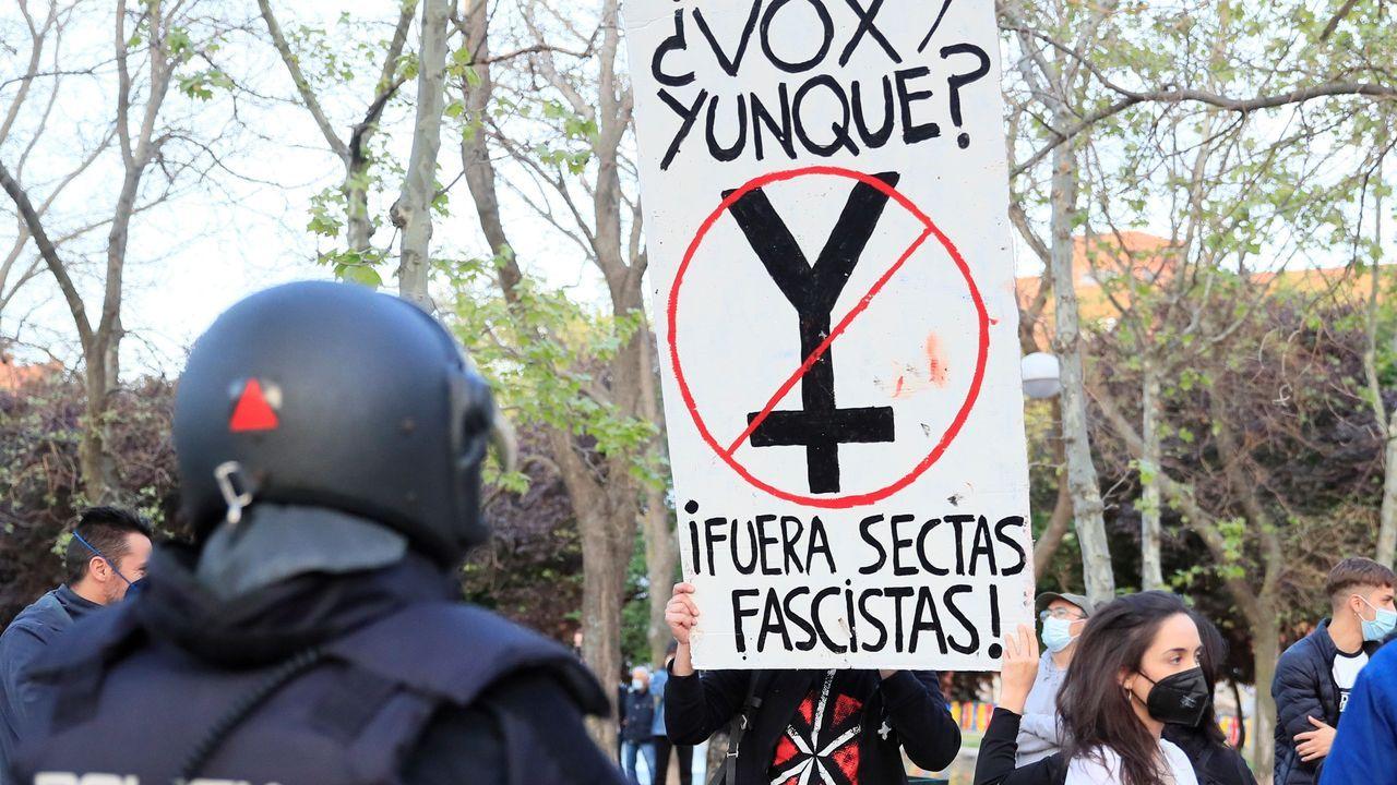 La policía nacional junto a manifestantes congregados en Vallecas para protestar por el acto de Vox