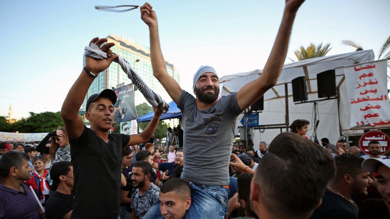 Un grupo de manifestantes celebran la dimisión del primer ministro