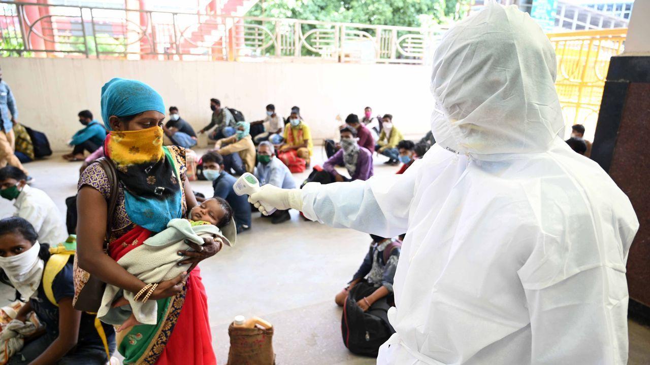 Un sanitario toma la temperatura a una mujer y su hija en La India